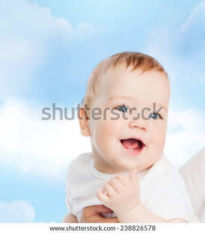 family, child and parenthood concept - close up of mother holding smiling baby - stock photo