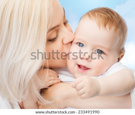 family, child and parenthood concept - happy mother kissing smiling baby - stock photo