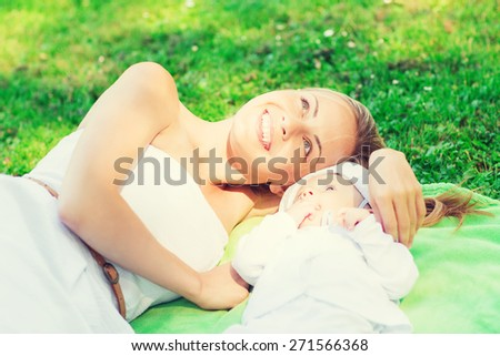 family, child and parenthood concept - happy mother lying with little baby on blanket in park - stock photo