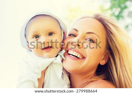 family, child and parenthood concept - happy mother with little baby outdoors - stock photo