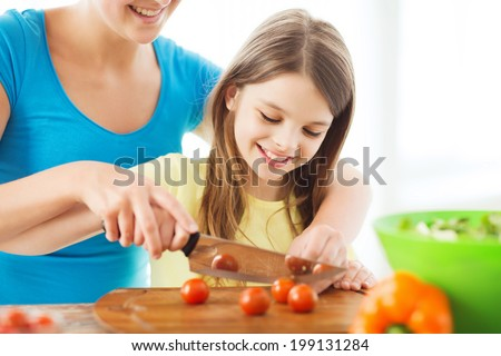 family, child, cooking and home concept - smiling little girl with mother chopping tomatoes in the kitchen - stock photo