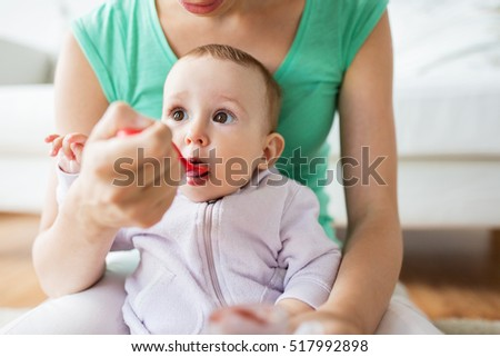 family, child, eating and parenthood concept - mother with spoon feeding little baby at home
