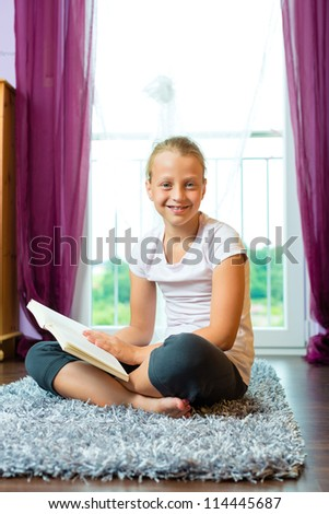 Family - child or teenager reading a book at home in the living room