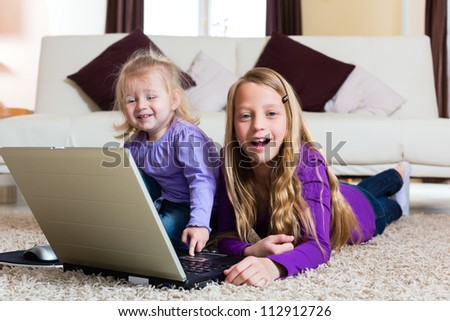 Family - child playing with the laptop lying on the floor, her little baby sister is with her