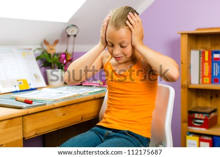 Family - child sitting at home at her desk and doing homework and she does not have much fun