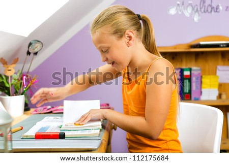 Family - child sitting at home at her desk and doing homework or prepare a poetry album - stock photo