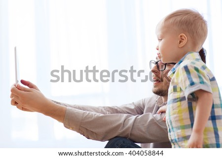 family, childhood, fatherhood, technology and people concept - happy father and son with tablet pc computer playing or having video chat at home - stock photo