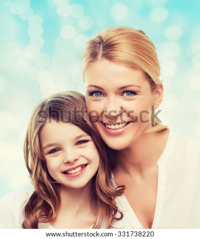 family, childhood, happiness and people - smiling mother and little girl over blue lights background - stock photo