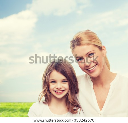 family, childhood, happiness and people - smiling mother and little girl over blue sky and grass background - stock photo