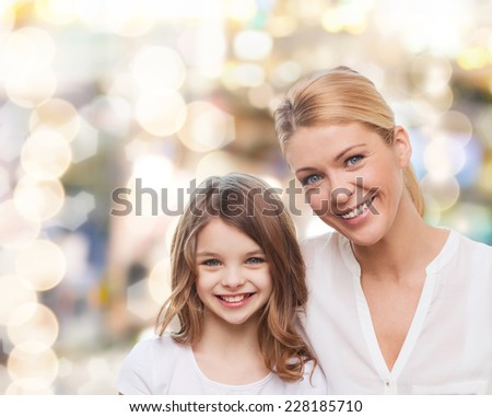family, childhood, happiness and people - smiling mother and little girl over lights background - stock photo