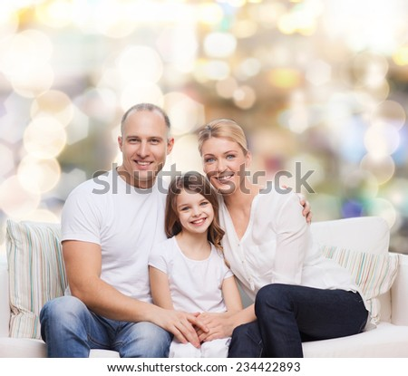 family, childhood, holidays and people concept - smiling mother, father and little girl over lights background