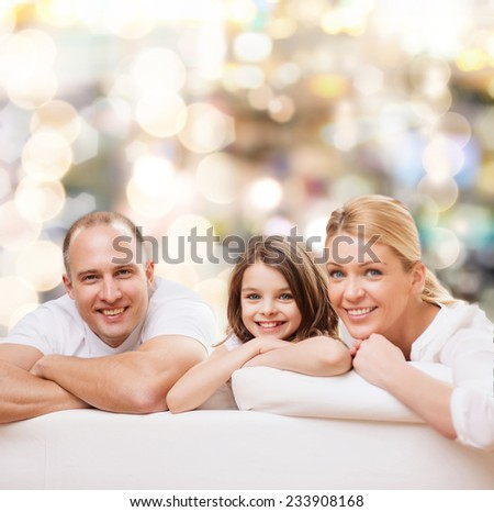 family, childhood, holidays and people - smiling mother, father and little girl over lights background - stock photo