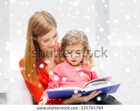 family, childhood, holidays, finances and people concept - happy mother and daughter with book at home