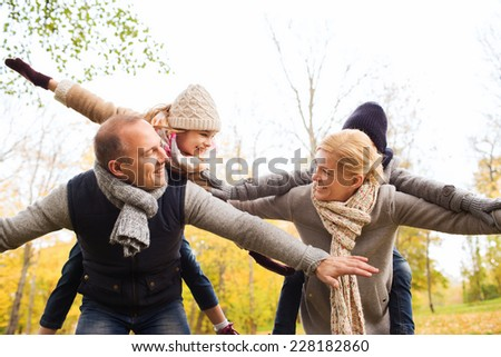 family, childhood, season and people concept - happy family having fun in autumn park - stock photo