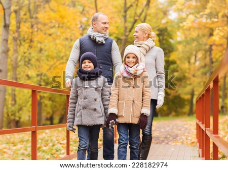family, childhood, season and people concept - happy family in autumn park
