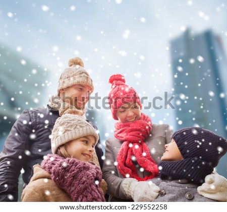 family, childhood, season and people concept - happy family in winter clothes over snowy city background - stock photo