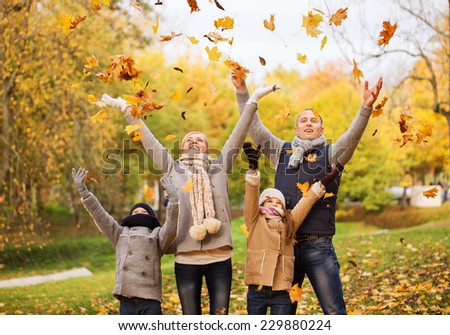 family, childhood, season and people concept - happy family playing with autumn leaves in park - stock photo