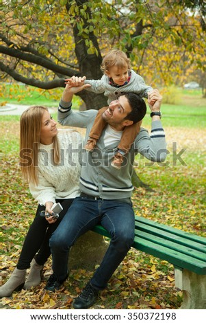 Family, childhood, season and people concept - happy family playing with autumn leaves in park.