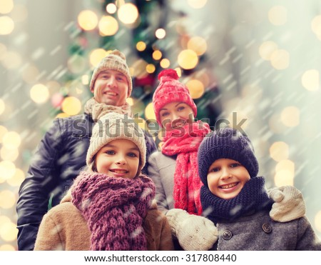 family, childhood, season, holidays and people concept - happy family in winter clothes over christmas tree lights background - stock photo