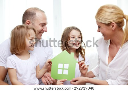 family, children, accommodation and home concept - smiling parents and two little girls at home with green house symbol - stock photo