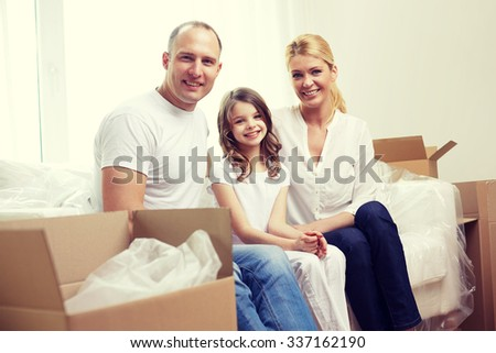 family, children, accommodation and people concept - happy family with boxes moving to new home - stock photo