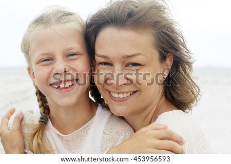 family. children and happy parent concept - hugging mother and daughter