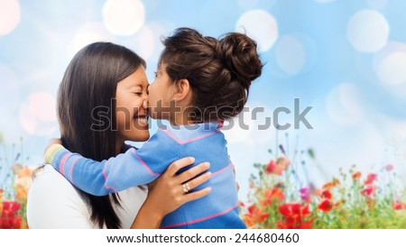 family, children and happy people concept - happy little girl hugging and kissing her mother over blue sky with lights and poppy field background - stock photo