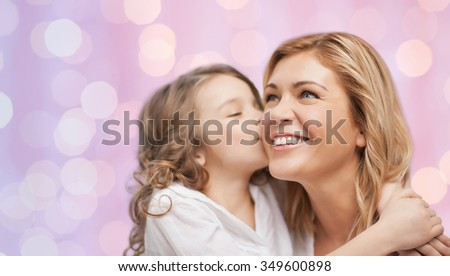 family, children and happy people concept - happy little girl hugging and kissing her mother over pink holidays lights background