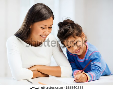 family, children and happy people concept - mother and daughter drawing - stock photo