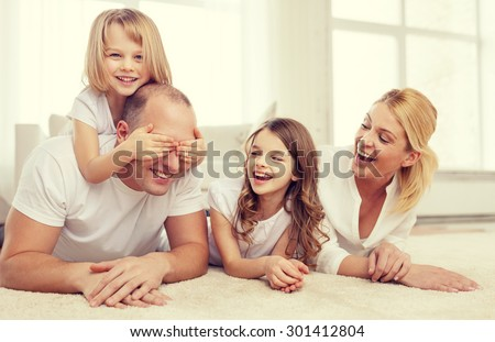 family, children and home concept - smiling family with and two little girls lying on floor at home and having fun - stock photo