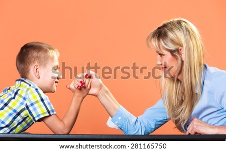 Family, children and motherhood concept. Son confronts his middle aged mother. Woman and little boy arm wrestling having fun.
