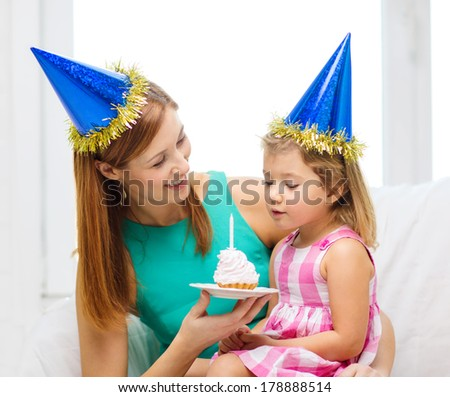 family, children, celebration and happy people concept - happy mother and daughter in blue party hats with cake and candle