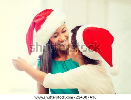 family, children, christmas  and happy people concept - hugging mother and daughter in santa helper hats - stock photo