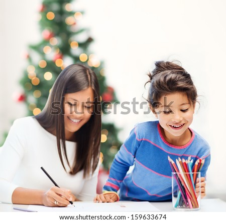 family, children, christmas, x-mas and happy people concept - mother and daughter drawing