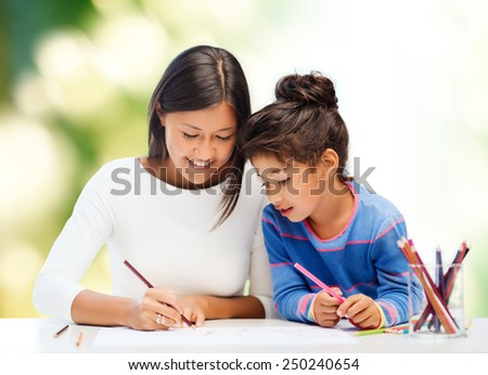 family, children, creativity and happy people concept - happy mother and daughter drawing with pencils over green background
