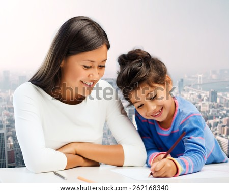 family, children, creativity and happy people concept - happy mother and daughter drawing with pencils over city background
