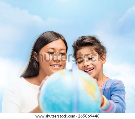 family, children, education, geography and people concept - happy mother and daughter with globe over blue sky background - stock photo
