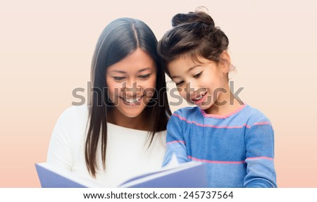 family, children, education, school and happy people concept - happy mother and daughter reading book over pink background - stock photo