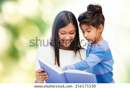 family, children, education, school and happy people concept - happy mother and daughter reading book over green background - stock photo