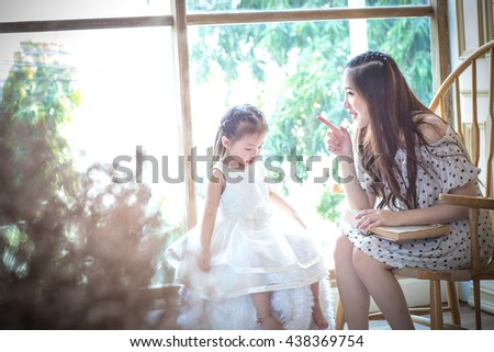 family, children, education, school and happy people concept - happy mother and daughter reading book .Backlit shot - stock photo