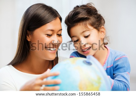 family, children, education, school and happy people concept - mother and daughter with globe - stock photo