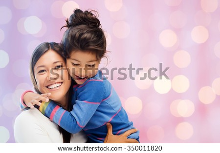 family, children, love and happy people concept - happy mother and daughter hugging over holidays lights background - stock photo