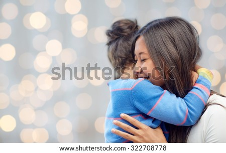 family, children, love and happy people concept - happy mother and daughter hugging over lights background - stock photo