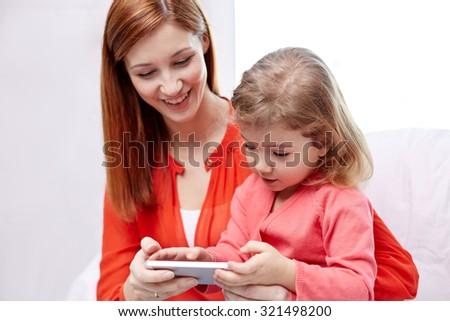 family, children, parenthood, technology and internet concept - happy mother and daughter with smartphone at home - stock photo