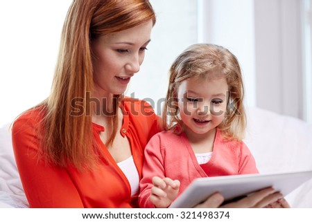 family, children, parenthood, technology and internet concept - happy mother and daughter with tablet pc computer at home - stock photo