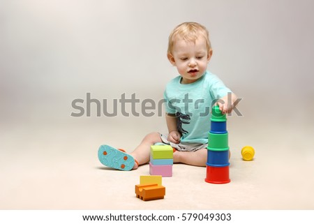 Family, children, people concept. Studio shot of cute little baby boy sitting on the floor and playing with some toys.