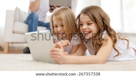 family, children, technology and home concept - smiling sister with tablet pc computer and parents on the back with laptop - stock photo