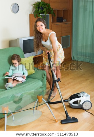 Family chores with vacuum cleaner in living room.  Focus on woman  - stock photo