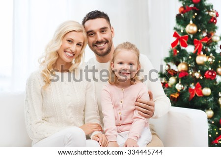 family, christmas, holidays and people concept - happy mother, father and little daughter sitting on sofa at home - stock photo
