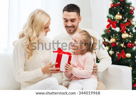 family, christmas, holidays and people concept - happy mother, father and little daughter with gift box sitting on sofa at home - stock photo